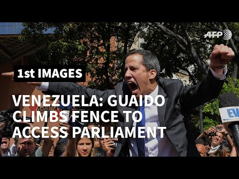 Venezuela's Guaido climbs on fence as access to parliament is blocked | AFP