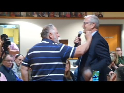 Watch a man stuff money in a GOP congressman\'s shirt at a heated North Dakota town hall