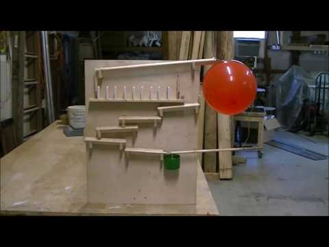 rube goldberg machine, science project. Dominoes falling in slow motions.