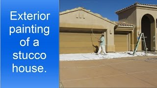 Spray painting exterior of a stucco house.