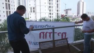 השמאלנים מופתעים: מה קרה כשאראל מרגלית הגיע בהפתעה לתלות שלטים במרפסת שלכם?