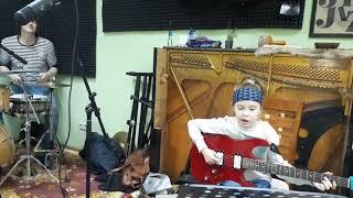 Репетиция музыкантов: супер-барабанщик и дети играют на электрогитаре