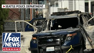 Suspect arrested after allegedly setting fire to police car with officer inside