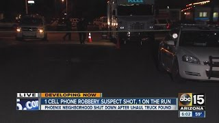 Armed robbery suspect shot by police; second suspect on the run