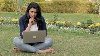 Girl sitting outside in a park and working on laptop