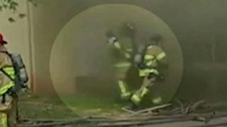 Hero firefighter catches baby dropped from burning building