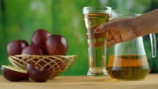 Closeup shot of an Indian woman's hands keeping a glass of apple juice on a wooden table