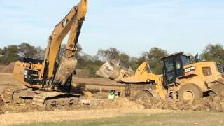 Huge front end loader stuck in the mud gets kids construction- help from a track hoe
