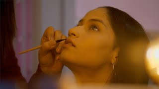 Young professional makeup artist applying lipstick to her client - Indian beauty