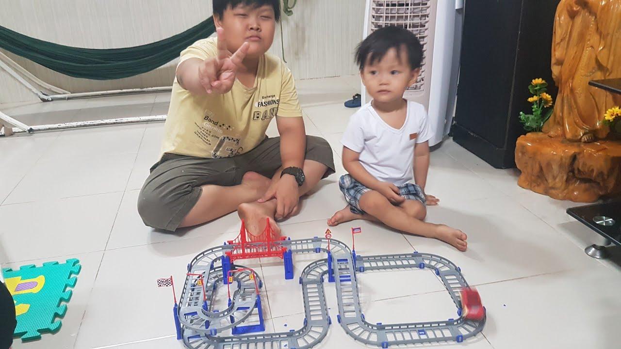 Tin và anh Hai chơi bộ đồ chơi xe đua trên đường ray