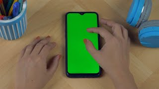 Overhead shot of an Indian female using her smartphone with green mock-up screen