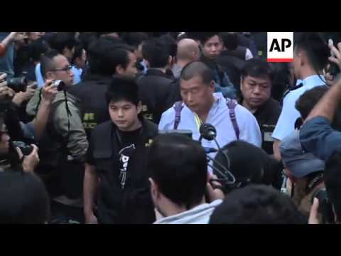 Police arrest and carry away protesters who were sitting in road