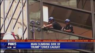 Police pull the man who was climbing Trump Tower into the building.