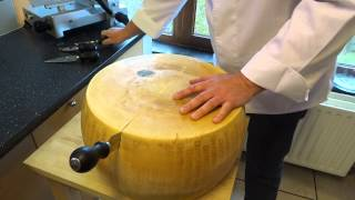 opening a wheel of parmesan cheese (parmigiano reggiano)