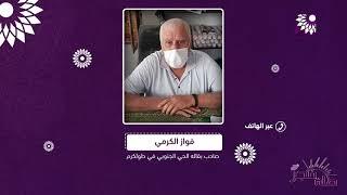 """مثال التاجر الملتزم، الحاج """"أبو هشام"""" يبرز شهادة التطعيم ويعلقها على حائط بقالته مرتديا كمامته"""