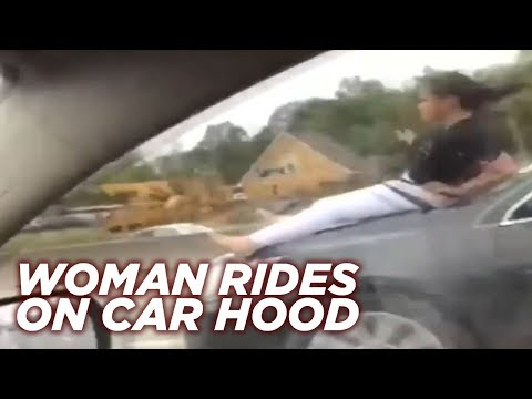 Woman rides on car hood down Houston highway