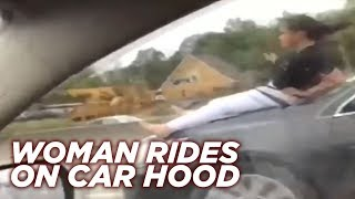 Woman rides on car hood down Houston highway