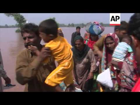 People flee flood waters with whatever possessions they can carry