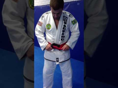 Coral belt Carlos Machado tying his belt.