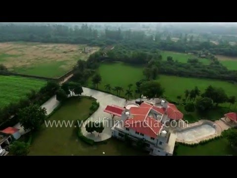 Flying over Gurgaon greenery, with a red farmhouse, and Aravalis