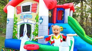 Little girl plays with dolls and builds huge inflatable houses