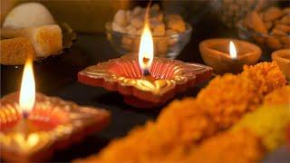Women placing beautiful lamp / diya in the temple for Diwali puja