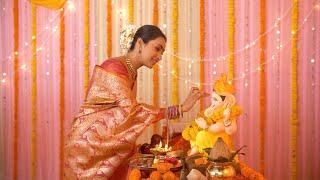 Cheerful Young Indian lady putting tilak on Lord Ganesh idol while praying - Ganesh Chaturthi