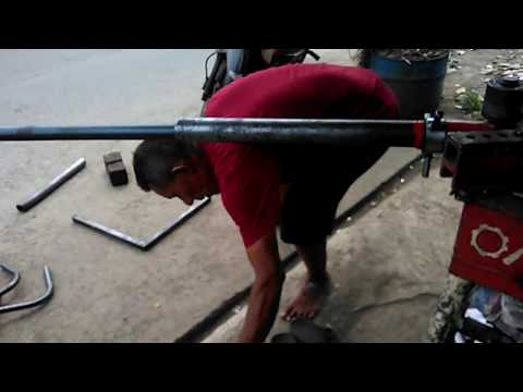 Bengkok pipa besi pake alat roll manual.