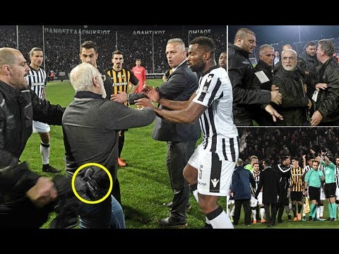 PAOK President Ivan Savvidis enters the field with a gun after referee disallowed a goal