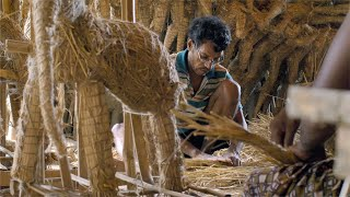 Shot of a worker making different shapes for Durga Ma idol by tying hay with rope