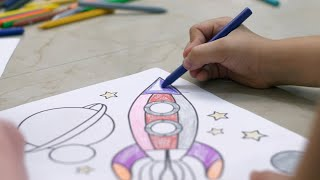 Kids coloring on a sheet of paper with crayons while sitting on the floor