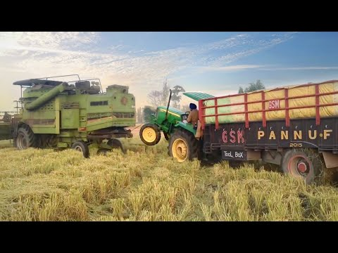 John deere 5050E With 18FT Fully Loaded Trolley Stucked in Muddy Field Pulled out With Combine