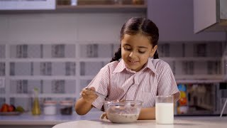 Beautiful little Indian girl having breakfast with cereals, milk in the kitchen - Health, Morning school routine