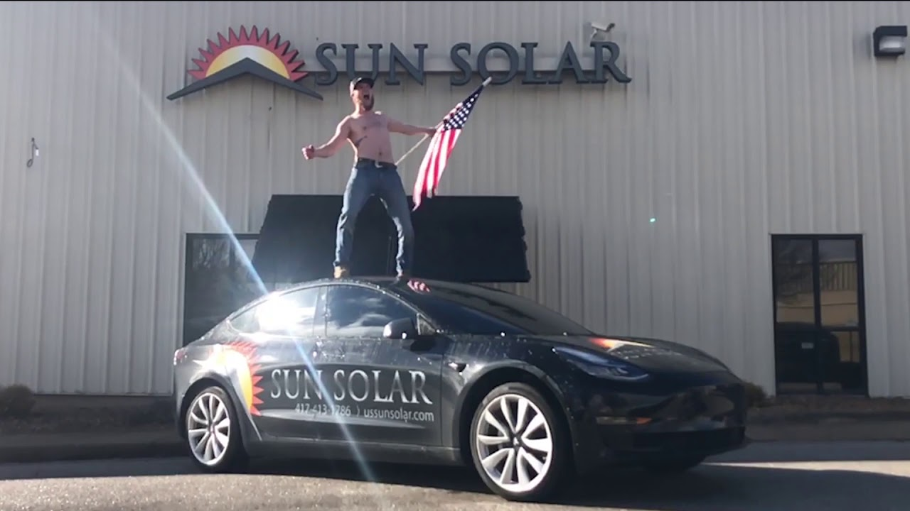 Guy Stands On Roof Of Tesla Model 3 Celebrates American Made Solar Panels