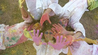 Group of happy young friends playing with organic Gulal colors - Holi festival, India