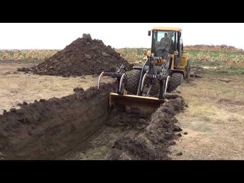 John Deere 624k high lift digging garbage hole