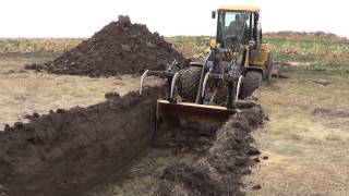 John Deere 624k high lift digging garbage hole