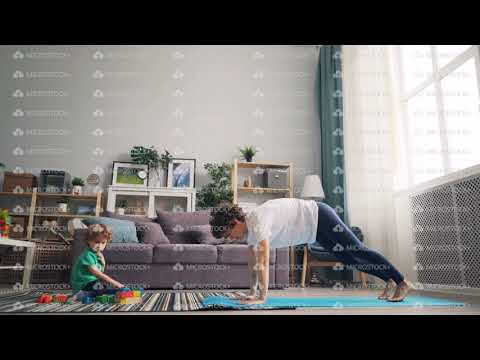 modern-housewife-doing-yoga-while-her-little-child-playing-with-blocks-on-carpet
