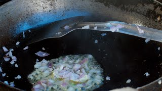Onions being fried and cooked in a huge frying pan at a local dhaba
