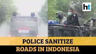 Watch: Police trucks in Indonesia hit the road to spray disinfectant