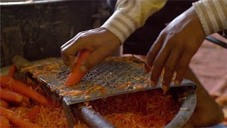 Closeup shot of an Indian man grating the carrot to prepare Gajar Ka Halwa (Famous Sweet in India)