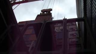Container loading into cargo hold of container ship. View from inside of the cargo hold
