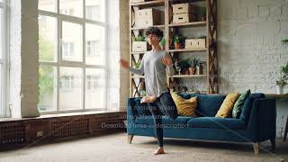 Slim yogini woman is doing yoga alone in modern loft style apartment balancing on one leg with hands