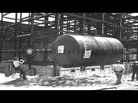 High rise steel building under construction. Crane swings wrecking ball. Fuel oil...HD Stock Footage