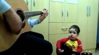Em bé dễ thương ôm guitar hát theo bố