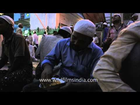 Muslim men eat together outside a mosque at Iftar - Delhi