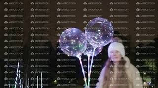 Cute happy girl holding illuminated balloons and ice skating in the evening