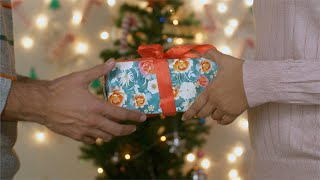 Close up shot of a man giving a Christmas gift to his loved one