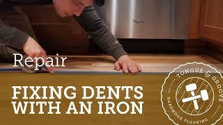 Repairing dents in a hardwood floor with an iron