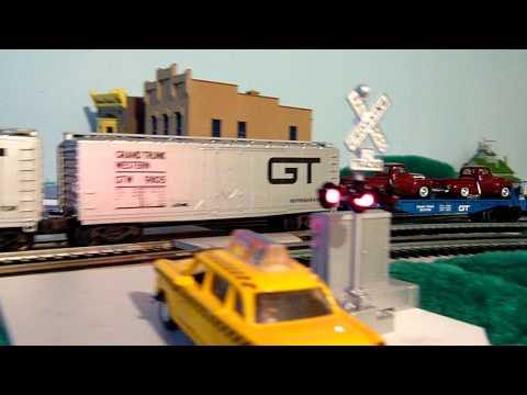 Lionel Grand Trunk Western GP7 and Switcher roll through the grade crossing with heavy freight.